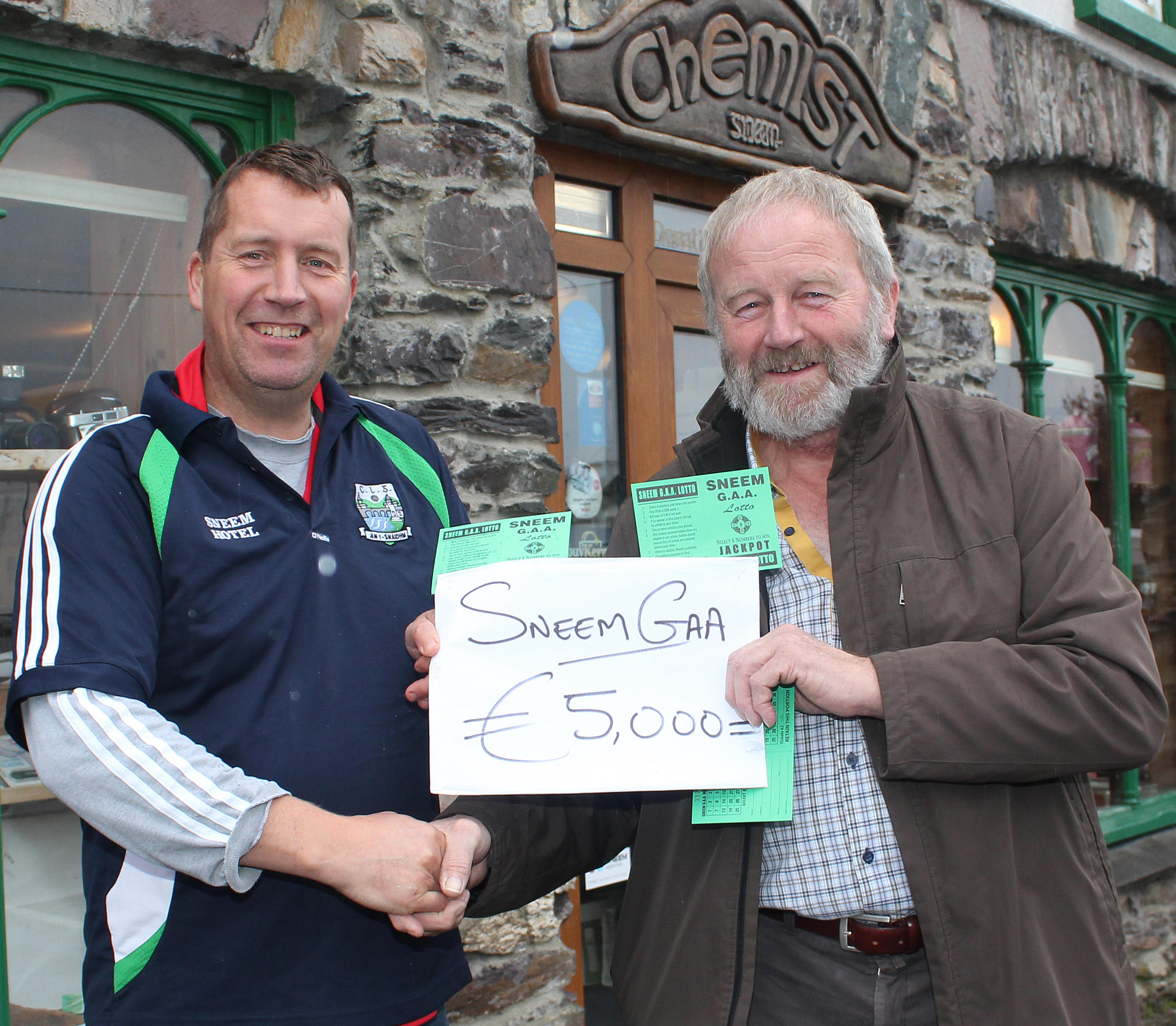 Keran Burns Chair of Sneem GAA Club presents George O'Neill with €5,000 from Sneem GAA Lotto Draw